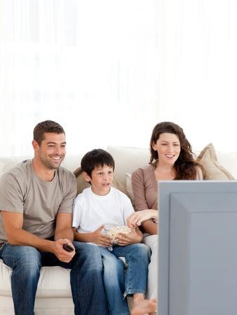 mujer viendo tv: Familia feliz viendo la televisi�n comiendo palomitas de ma�z juntos