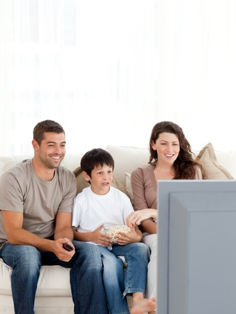 Happy family watching television while eating popcorn together photo