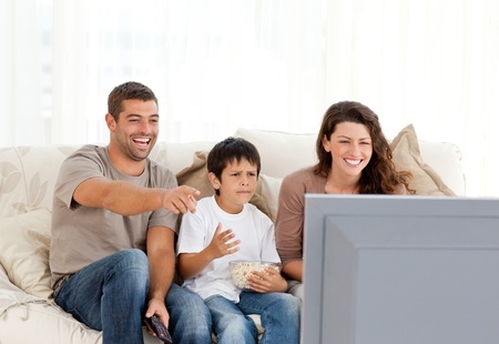 woman watching tv: Family laughing while watching television together