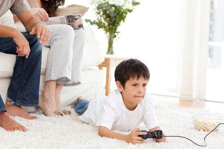Cute boy playing video game lying on the floor at home photo