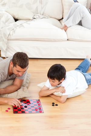 parlour games: Father and son playing checkers together lying on the floor