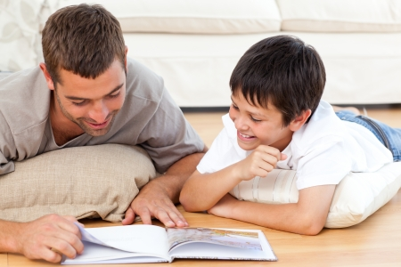 stories: Happy father and son reading a book together on the floor