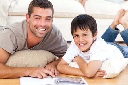 dad and son: Portrait of a father and son reading a book together on the floor Stock Photo