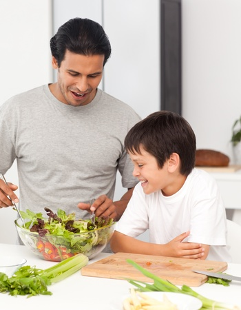 Handsome man preparing a salad with his son photo