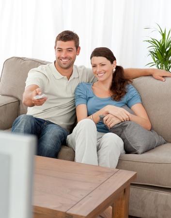 humoristic: Hombre feliz cambio de canal mientras est� viendo televisi�n con su esposa Foto de archivo
