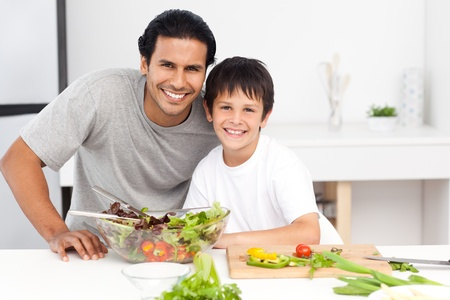 hispanic boy: Portrait of a father and his son preparing a salad