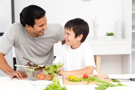 aceite de cocina: Adorable padre e hijo mirando mutuamente en la cocina Foto de archivo