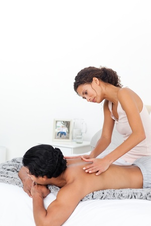 massaging: Attentive woman doing a massage to her boyfriend on their bed