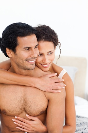 latin couple: Passionate woman hugging her boyfriend sitting on their bed