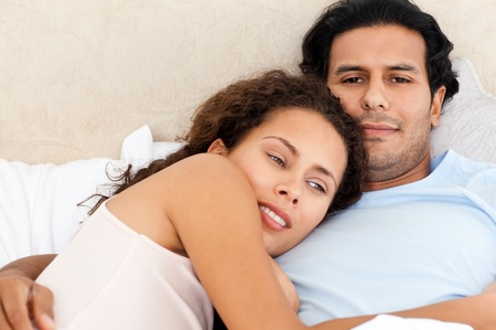 day bed: Portrait of a passionate couple lying together on their bed Stock Photo