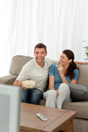Cheerful couple eating pop corn while watching a comic movie photo