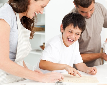 Cheerful family having fun while preparing biscuits together photo