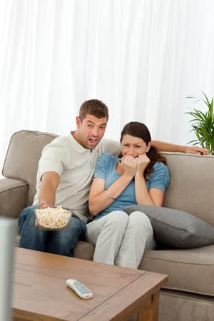 Terrified couple watching a horror movie in the living room photo