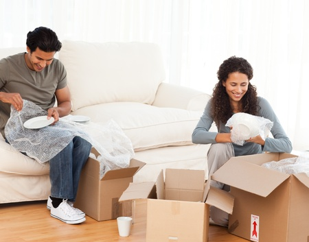 unpacking: Joyful couple packing glasses together in the living room