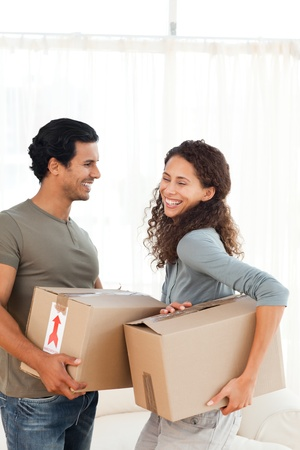 Lovely couple holding cardboards in their living-room photo