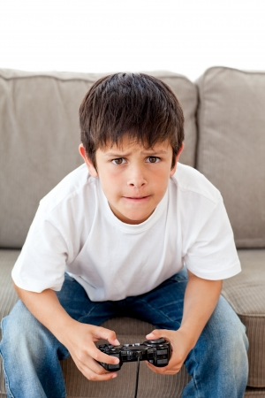 child alone: Cute boy playing video games sitting on the sofa