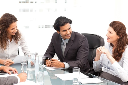 Businessman and businesswomen talking together around a table  photo