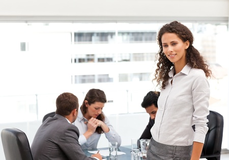 Attractive manager standing in the office while her team working photo