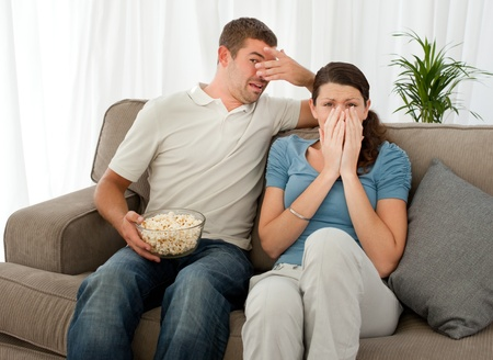 Scared couple eating pop corn while watching a horror movie photo