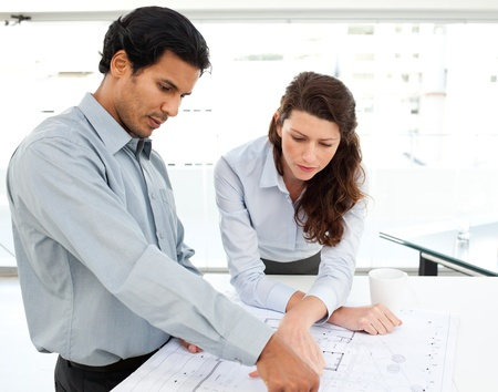 Two serious architects looking at blueprints on a table photo