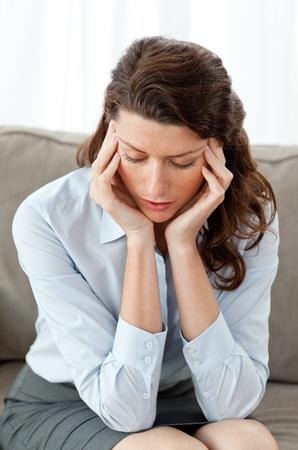 Pretty businesswoman having a headache sitting on the sofa Stock Photo