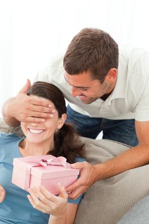 Gl�ckliche Frau erh�lt ein Geschenk von ihrem Freund im Wohnzimmer Lizenzfreie Bilder