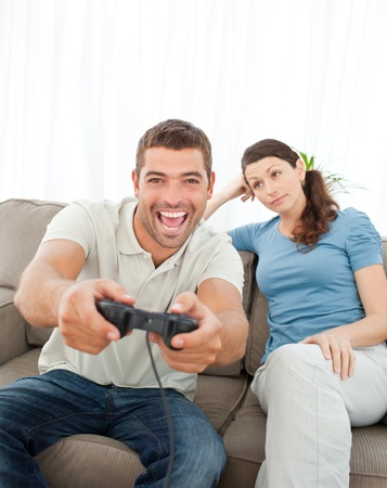 playing video games: Bored woman looking at her boyfriend playing video game on the sofa  Stock Photo