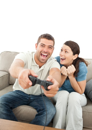 Cheerful woman encouraging her boyfriend playing video game photo