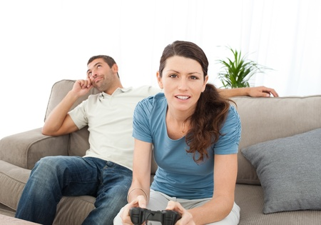 Serious woman playing video game while her boyfriend waiting for her on the sofa photo