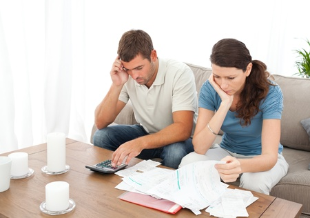 Desperate couple doing their accounts sitting on the sofa Stock Photo - 10207742