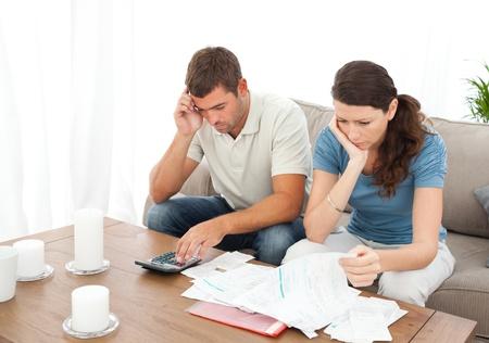 desesperado: Pareja desesperada haciendo sus cuentas sentado en el sof�