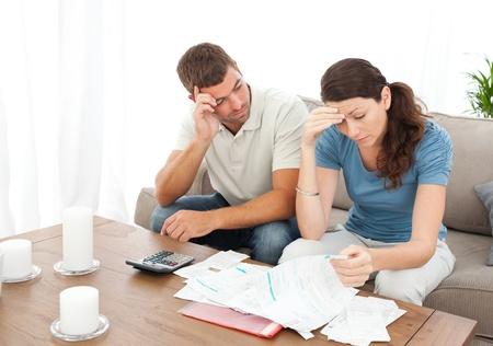 Couple inquiet faisant leurs comptes dans la salle de séjour Banque d'images