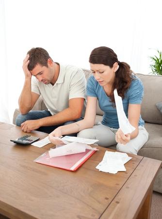 schuld: Bezorgd echtpaar te kijken naar hun rekeningen in de huiskamer Stockfoto