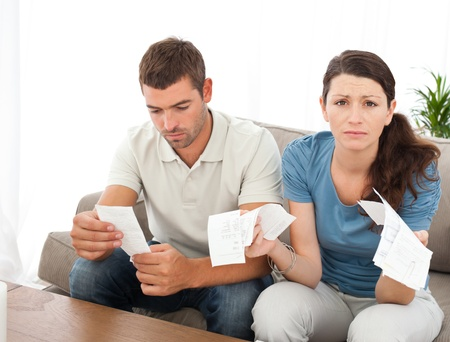 Desperate woman doing her accounts with her boyfriend sitting on the sofa Stock Photo - 10206817