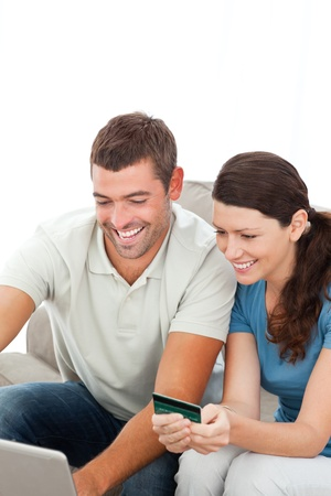 Happy couple buying online together sitting on the sofa photo