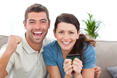 Portrait of a happy couple holding their credit card on the sofa photo