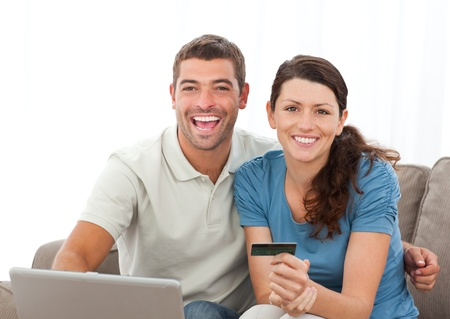 Cute couple with their laptop and credit card sitting in the living room photo
