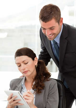 Serious businesswoman taking notes while discussing with her colleague photo