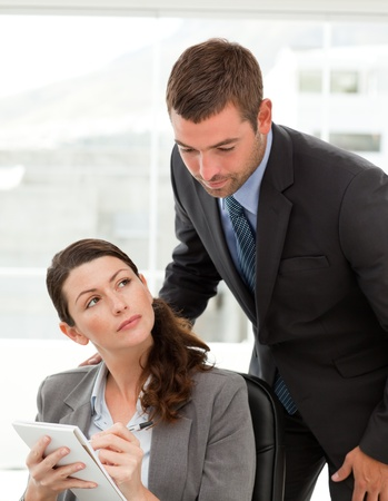 Handsome manager talking with her secretary in the office  photo