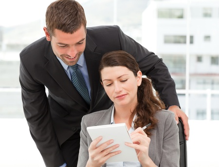 Happy businessman helping a businesswoman working at her desk photo