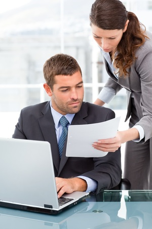 Two business people looking at a paper while working on the laptop photo