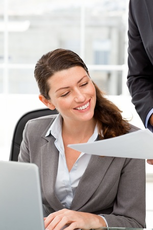 Happy businesswoman reading a paper while working on laptop photo