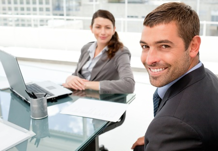Fr�hlich Gesch�ftsleute arbeitet an einem Laptop w�hrend einer Sitzung Stockfoto