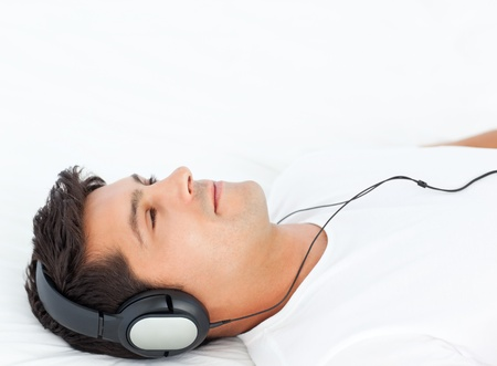 listen music: Charismatic man listening music lying on his bed