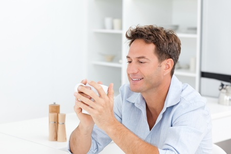 Attractive man drinking coffee sitting at a table Stock Photo - 10170963