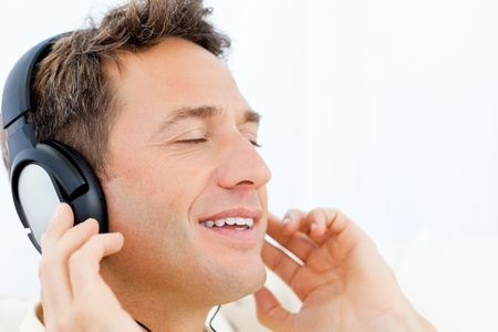 Peaceful man listening music on the sofa Stock Photo - 10172603