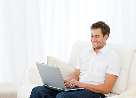 Handsome man working on his laptop while relaxing on the sofa Stock Photo - 10163662
