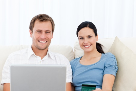 Relaxed couple with laptop and credit card sitting on the sofa Stock Photo - 10171206