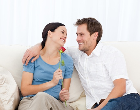 Beautiful woman holding a rose sitting on the sofa Stock Photo - 10163261