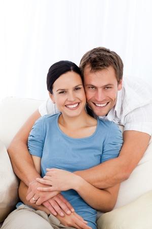 pareja de esposos: Retrato de un hombre feliz abrazando a su novia mientras se relaja en el sofá Foto de archivo